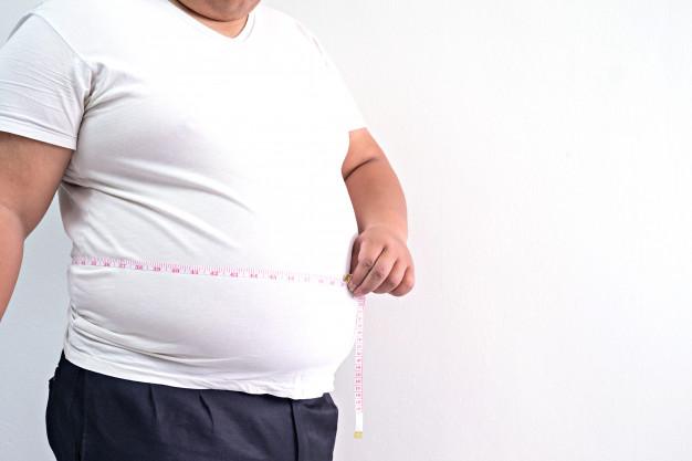 hombre con obesidad midiendo su barriga.